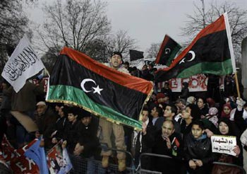 تظاهرات در جلو سفارت لیبی در لندن با پرچم قدیمی- اینگونه هماهنگی و همایش در برابر بیشتر سفارت خانه های لیبی در سراسر جهان برپا بوده، و همچنین ادامه دارد.