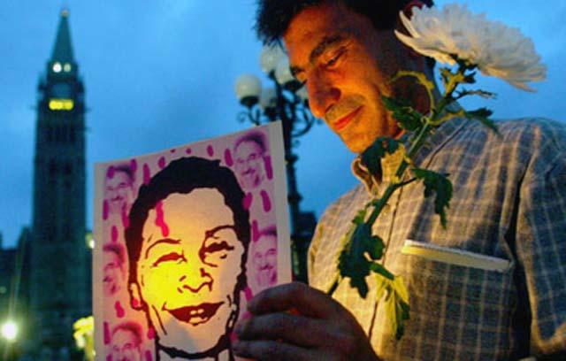 این تصویر زهرا کاظمی گزارشگر کانادایی در دست یک ایرانی به نام آقای شاهپور رهانام  می باشد که در مجلس یادبودی باروشن کردن شمع در ژوییه ۲۰۰۳ در کانادا  شرکت نموده است. زهرا کاظمی یکی از صدها قربانی زن سیستم زن ستیز اسلام ولایت وقیح است، که بر اثر ضربه هایی که بر سر او وارد کرده بودند، جان سپرد، و به دستور رژیم کشتارگر، پیکر او را بدون هر تشریفات و یا آگاهی عمومی در شیراز به خاک سپردند.