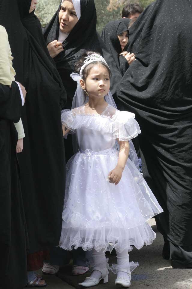 در این جا دختر بچه ای که باید به دبستان رود، در پوشش زناشویی دیده می شود. این فرتور ما را به یاد پیامبر اسلام می اندازد که دختر بچه ۹ ساله را به رختخواب برد.
