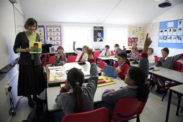 کلاس درسی در اروپا- شمار دانشجویان کم، نشسته به دور هم و با شرکت یکدیگر در آموزش و بحث و گفتگو با آموزگار. این روش ایدآل شناخته شده در تربیت و پرورش کودکان است که تنها در کشورهای آزاد و دمکرات با درآمد خوب فامیلی امکان پذیر است.