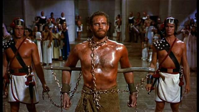 صحنه ای از فیلم ده فرمان، که موسی را به عنوان برده نشان می دهد که او را به حضور فرعون میبرند.