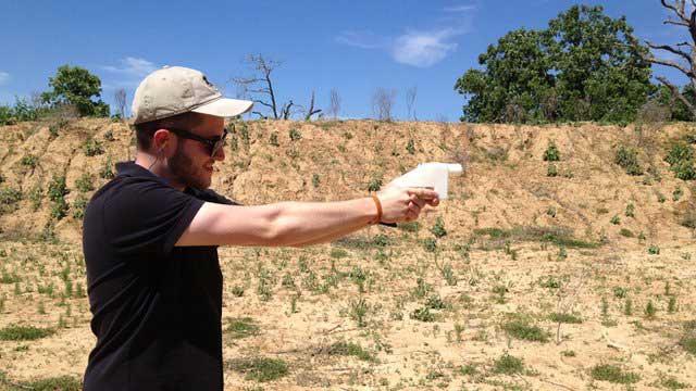 در این جا مردی تفنگ پلاستیکی را آزمایش می کند و کاربرد آن را با تفنگ فلزی معمولی مقایسه می نماید.