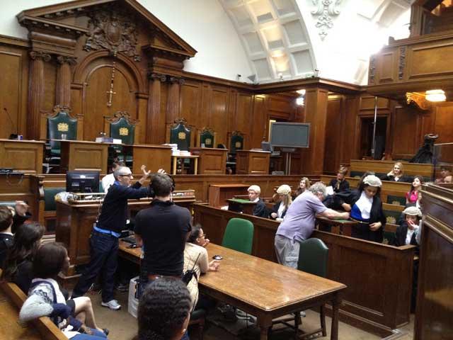 یک صحنه از نشست دادگاه در انگلیس پیش از برگزاری و تشکیل جلسه رسمی. درست با دادگاههای ما که در آن یک یا چند آخوند فرومایه و بی سواد دیده می شود، قابل مقایسه است.