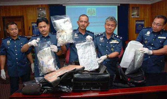 مأمورین مرزی و پلیس مالزی مواد مخدر گرفته شده از مسافرین را نشان می دهند. گویا از بسیاری از ایرانیان که همه روزه در مالزی به اتهام قاچاق دستگیر می شوند، شمار زیادی از آنها پس از بررسی تبرئه می گردند و بیگناه شناخته می شوند،