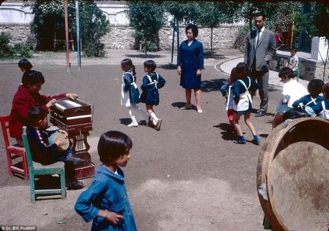 در این تصویر دانش آموزان با یونیفورم آبی رنگ دیده می شوند که با موزیک به پایکوبی و دست افشانی می پردازند.
