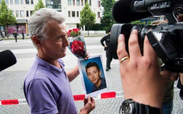 پدری (Naim Zabergja) عکس کودک خود (Dijamant) را که قربانی این جنایت شده در دست گرفته است.